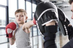 Ein Kind schlägt mit Boxhandschuhen in die Pratzen von seinem Trainer