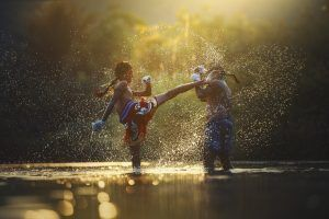 Zwei Muay Thai Kämpfer mit den Füßen im Wasser die kämpfen.