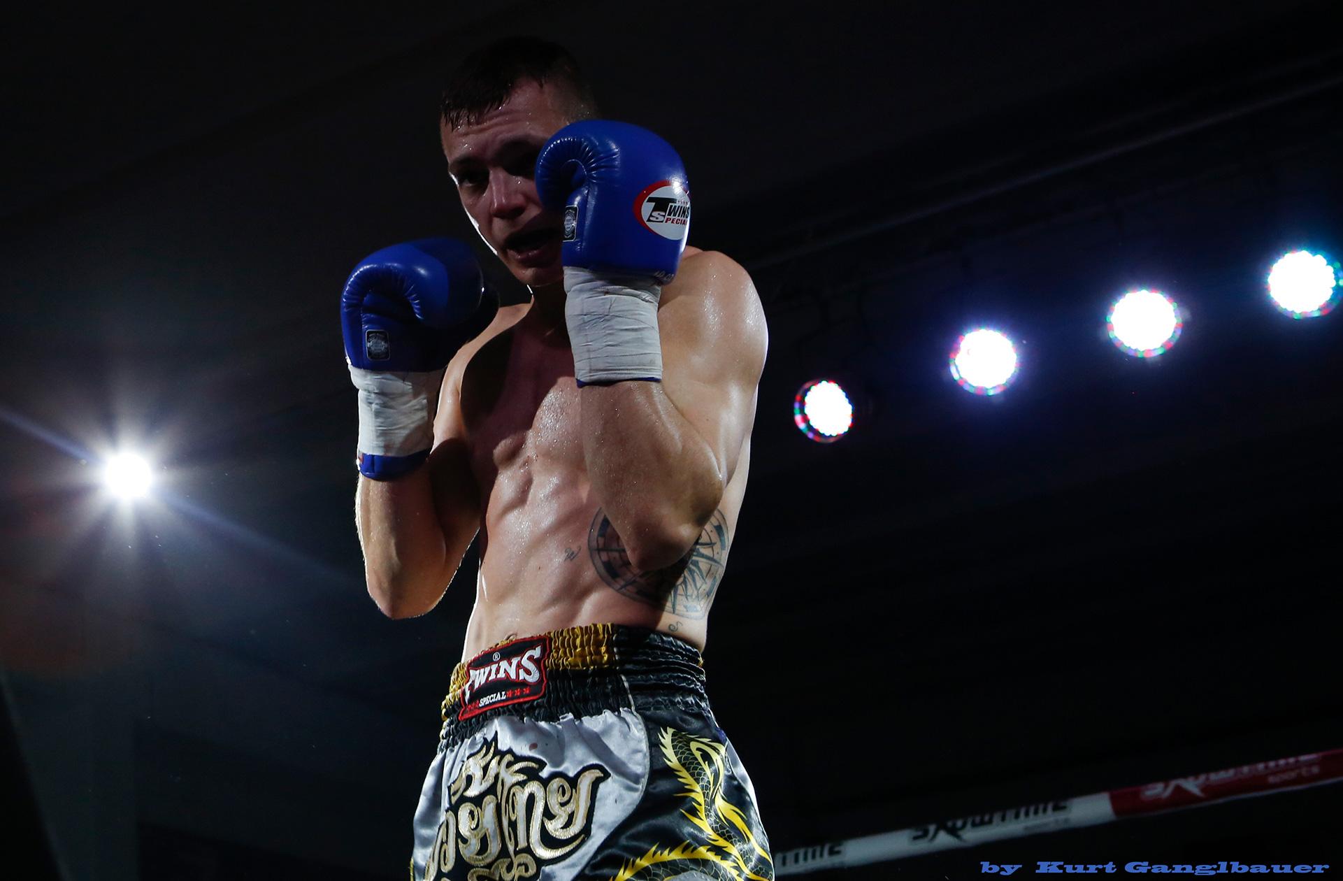 Ein Kämpfer im Ring mit Scheinwerfern beleuchtet.