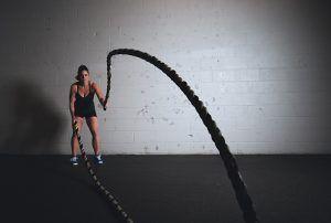 Eine Frau beim High Intensity Intervall Training mit zwei 'Battle Ropes' die sie schwingt.