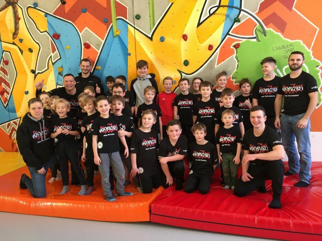 Ein Gruppenfoto mit den Kindern und Trainern der Muay Thai Academy Rohrbach im Aigo Kinderhotel in Aigen-Schlägl.