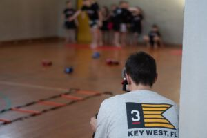 Ein Mann filmt mit einer Kamera Kinder beim Trainieren.