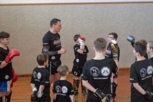Trainer erklärt Kindern eine Übung.