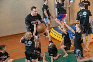Kinder zeigen aufgeregt auf um vom Trainer für das nächste Spiel ausgewählt zu werden.