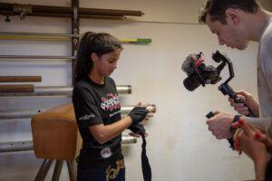 Eine Jugendliche die beim Bandagieren gefilmt wird.